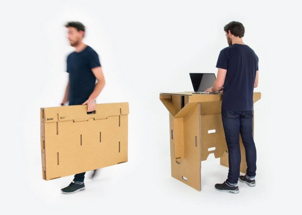 Man carrying a folded up cardboard desk and man standing at cardboard standing desk working on a laptop